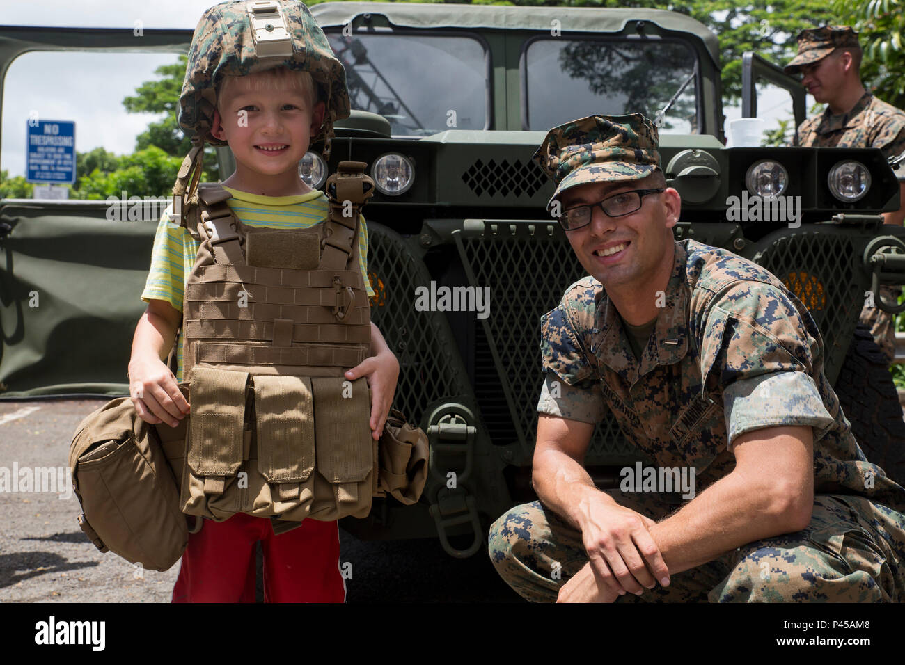 """KANEOHE, Hawaii – 1st Lt. Jacob Richardson, the headquarters platoon commander for Alpha Battery, 1st Battalion, 12th Marine Regiment and a Collierville, Tenn., native, poses for a photo with a child wearing a flak jacket and kevlar helmet during a """"Meet the Community Heroes"""" event at the Kaneohe Public Library in Kaneohe, Hawaii, June 23, 2016. The Marines were given the opportunity to interact with children and parents from the community. Children got the chance to meet police officers, firefighters and Marines. Multiple vehicles from the organizations were on display for all the children to - Stock Image"""