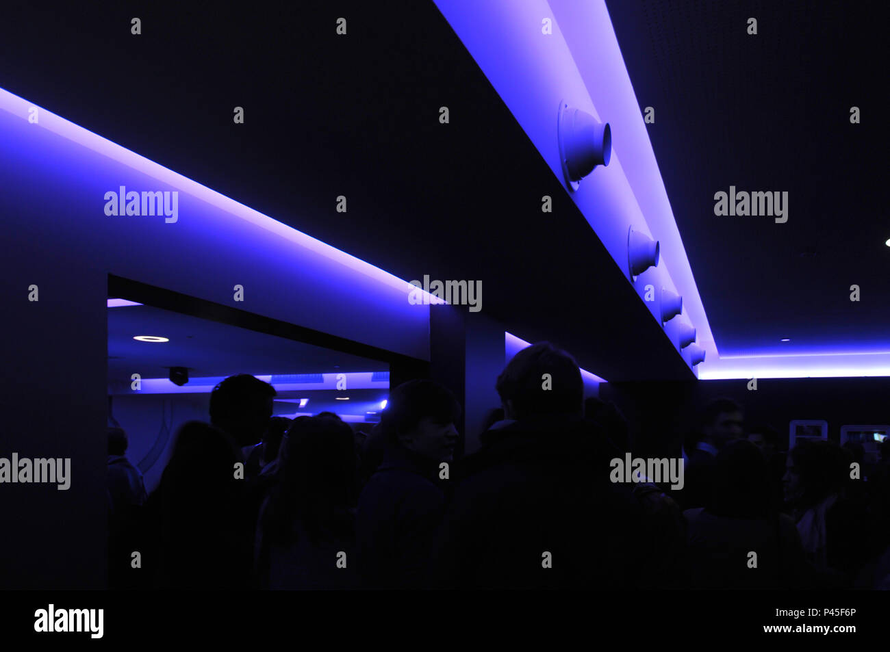People in a nightclub with blacklight - ultraviolet light - Stock Image