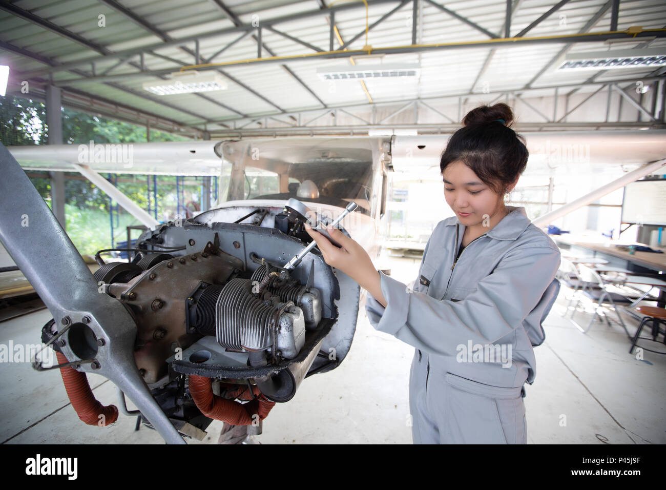 Asian men and women Engineers and technicians are repairing aircraft. - Stock Image