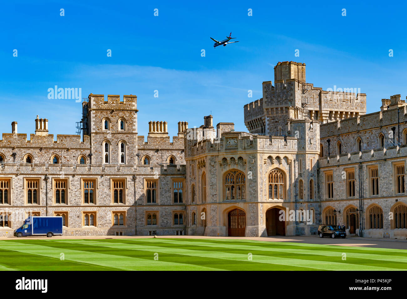 Airplane flying over group of buildings at Windsor Castle, a royal residence at Windsor in county of Berkshire, England, UK - Stock Image