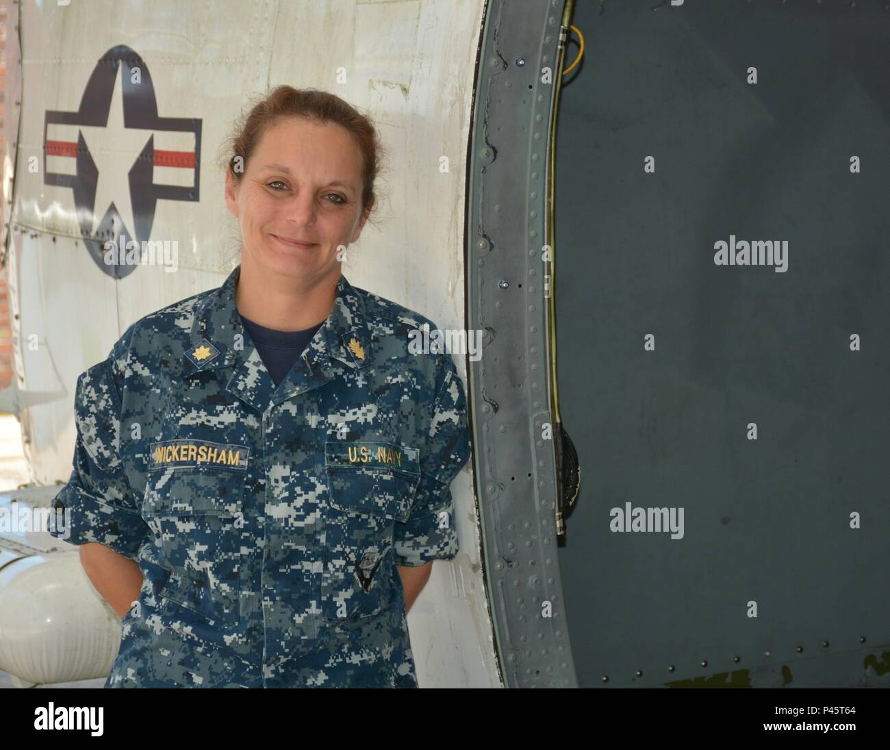 PENSACOLA, Fla. (June 8, 2016) Lt. Cmdr. Malissa Wickersham, the Flight Medic Course (FMC) department head at the Naval Aerospace Medical Institution (NAMI) stands with one of the FMC's simulation airframes. NAMI launched the Navy's first Flight Medic Course July 11. (U.S. Navy Photo by Hospital Corpsman 2nd Class Matthew Clutter/Released) - Stock Image