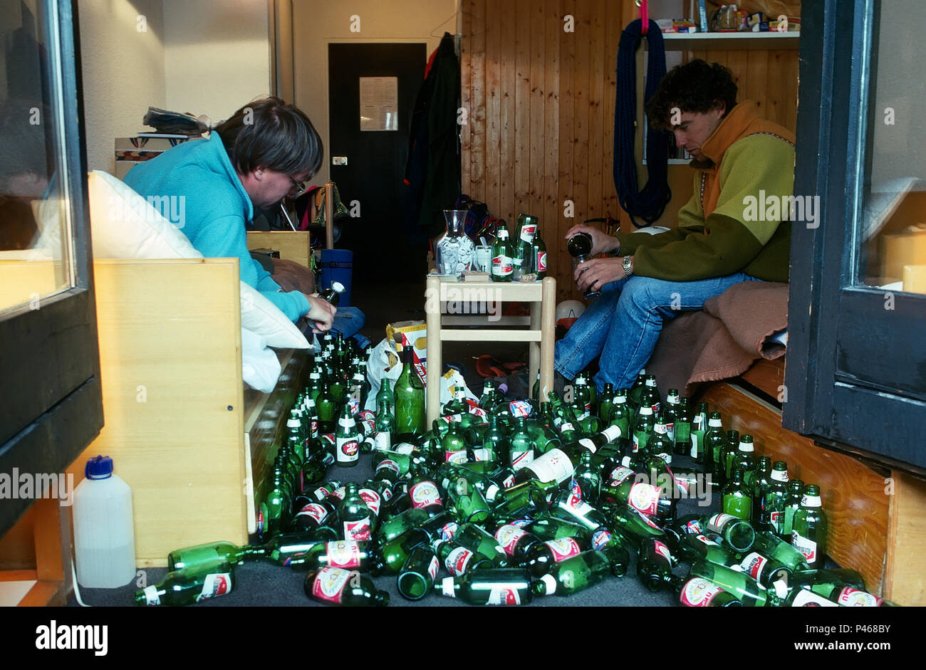 A quiet night in - two young men opening a beer bottle each, surrounded by empty bottles - Stock Image