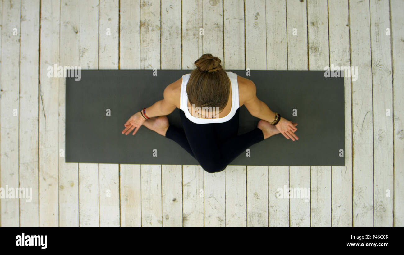 Sporty beautiful young woman practicing yoga, sitting in cross legged position - Stock Image