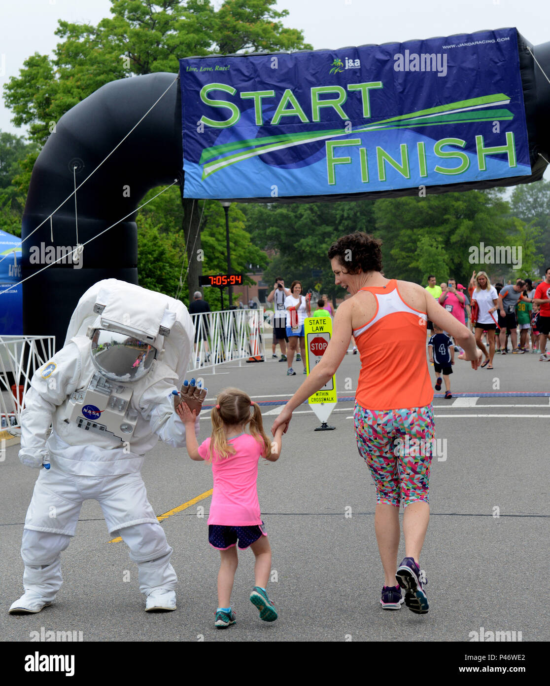 A NASA astronaut high-fives a child as she reaches the finish line of the  Kids one-mile event during the NASA Langley Research Center Moonwalk and  Run 5K at ... 4692a55ce50a
