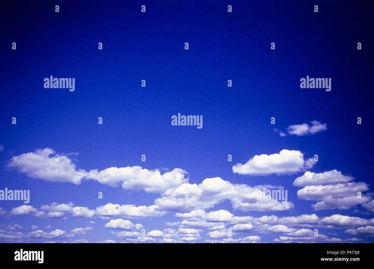 Blue sky with fluffy white clouds - Stock Image