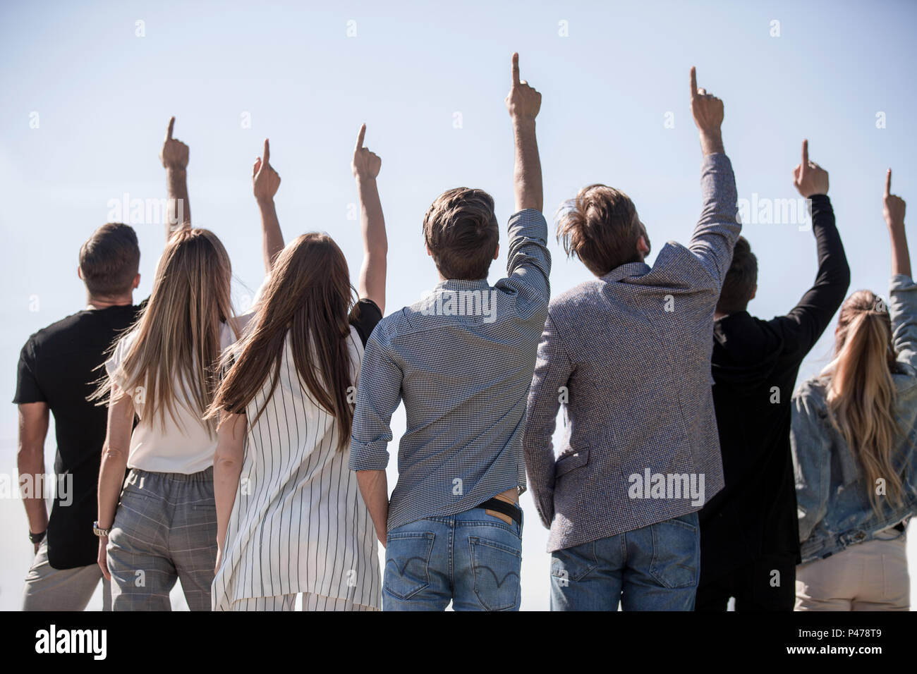 rear view . a group of friends showing up at a copy space - Stock Image