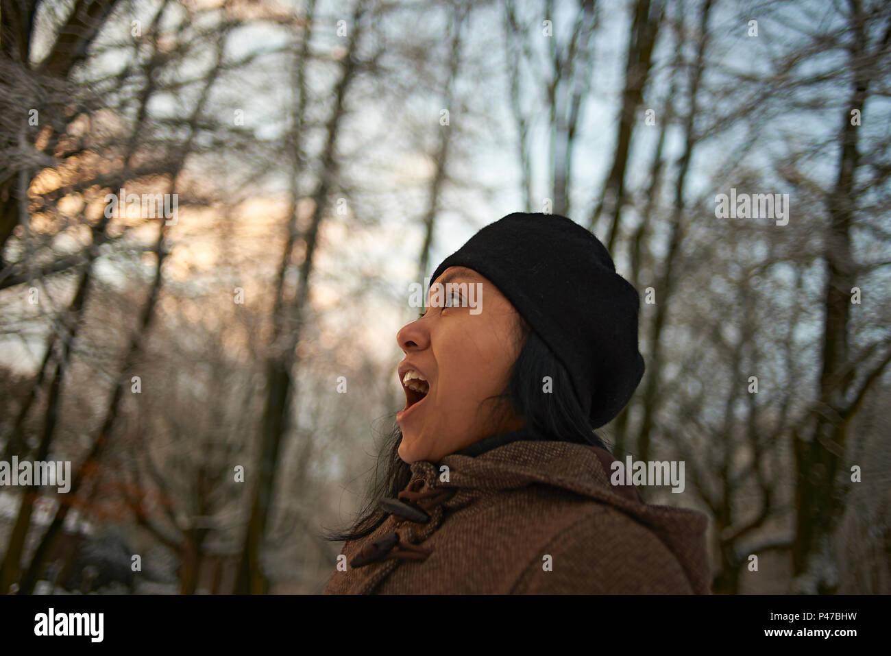 Profile view of an Asian woman in winter clothing in a forest at sunrise experiencing first snow in winter sunshine Stock Photo