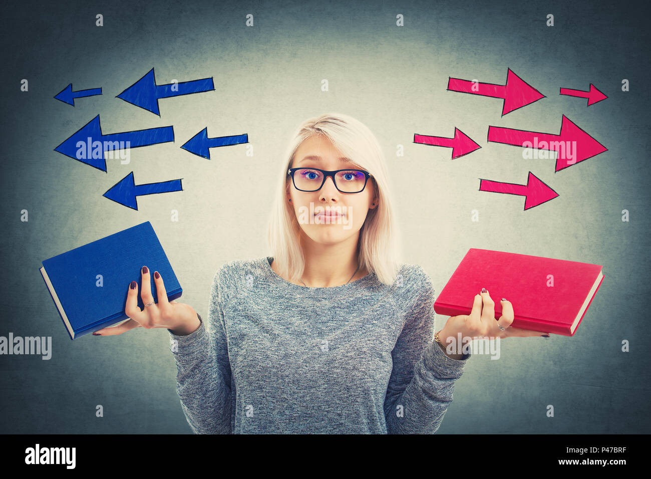 Confused young woman choosing between two books, red and blue, with arrows poinded to the left and right side. Difficult decision, education concept,  - Stock Image