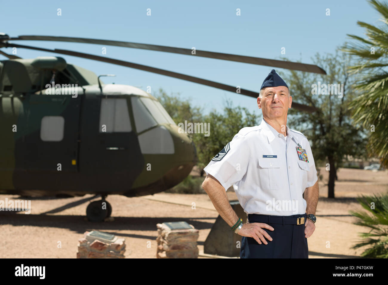 Chief Master Sgt. (ret.) Craig Bergman stands in front of the HH-3 'Jolly Green Giant' at Davis-Monthan Air Force Base, Ariz., May 19, 2016. Bergman retired as the maintenance superintendent for the 943rd Maintenance Squadron in 2007, having been one of five U.S. Air Force Reserve Airmen to establish the 71st Special Operations Squadron and bring the HH-3 here. His family's military legacy dates back to World War I. (U.S. Air Force photo by Tech. Sgt. Carolyn Herrick) - Stock Image