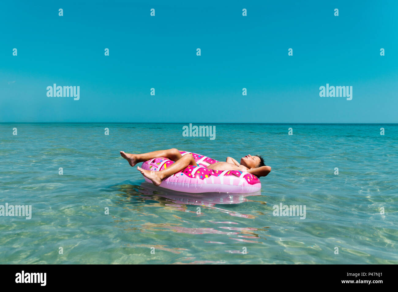 Relaxing boy in inflatable ring in sea. - Stock Image