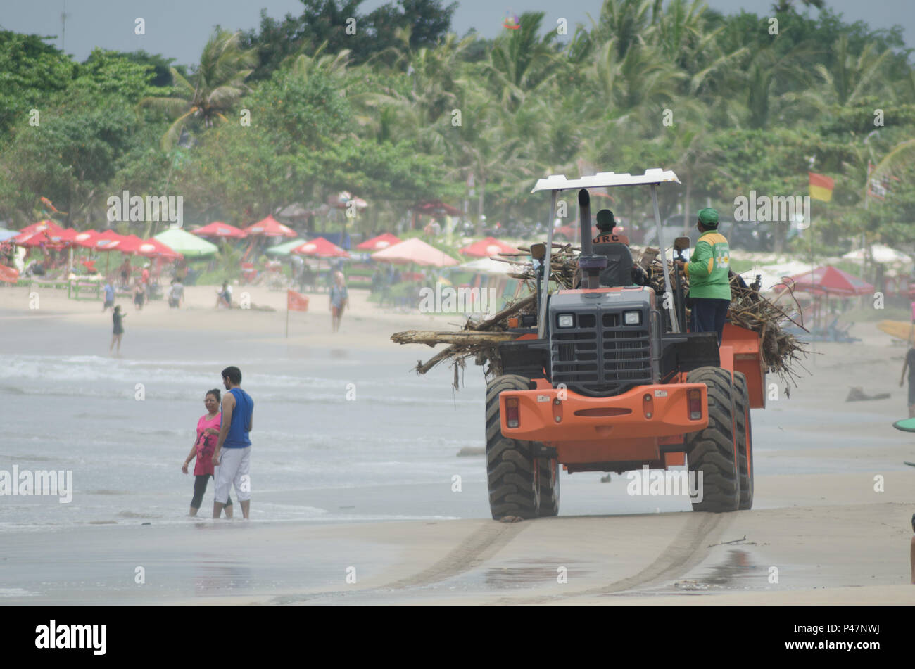 cleaning up trash in Kuta Beach, Bali Indonesia. Kuta is one of the most popular beaches in the world. - Stock Image