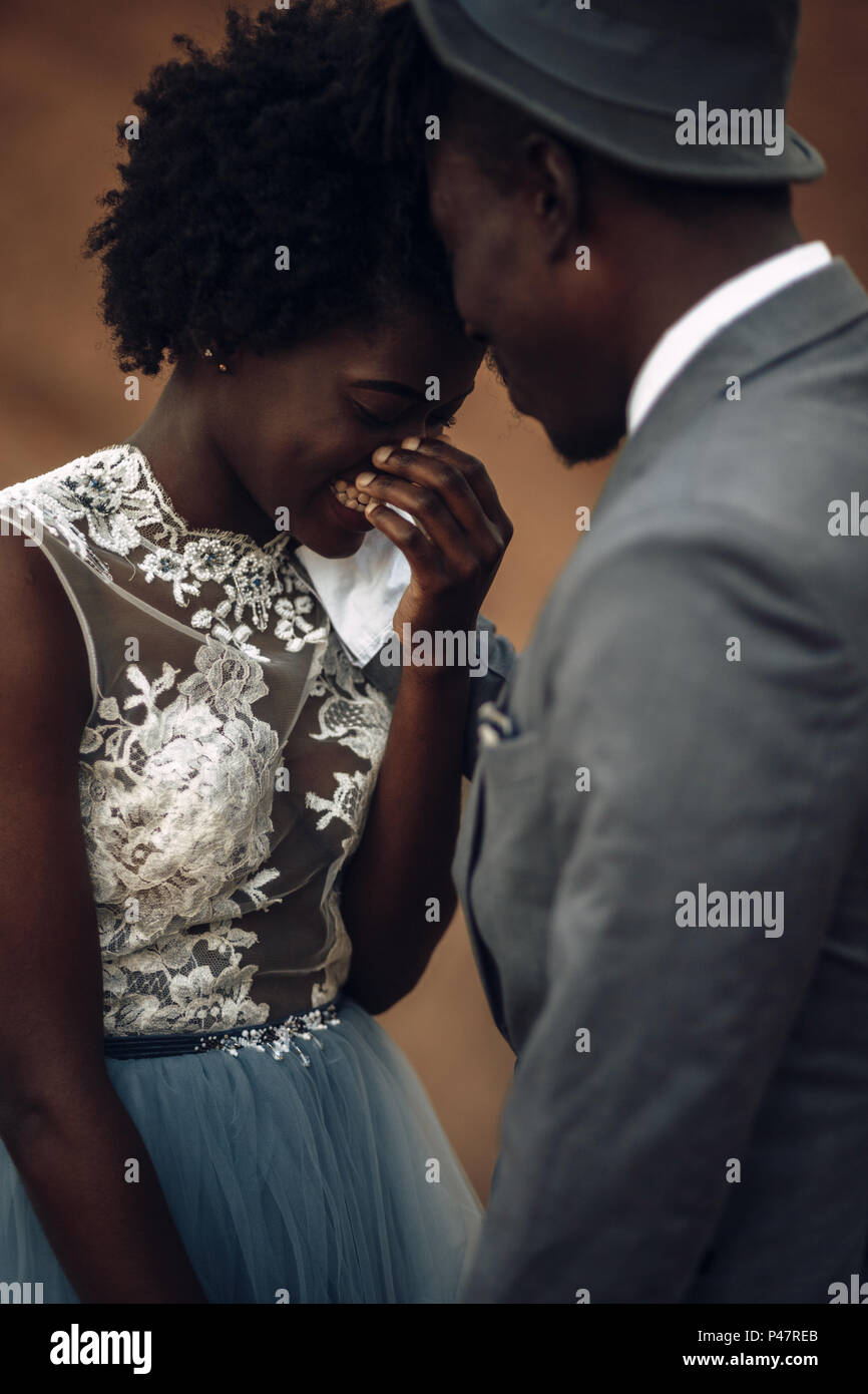Black happy newlyweds stand and cheerful laugh. Closeup. - Stock Image