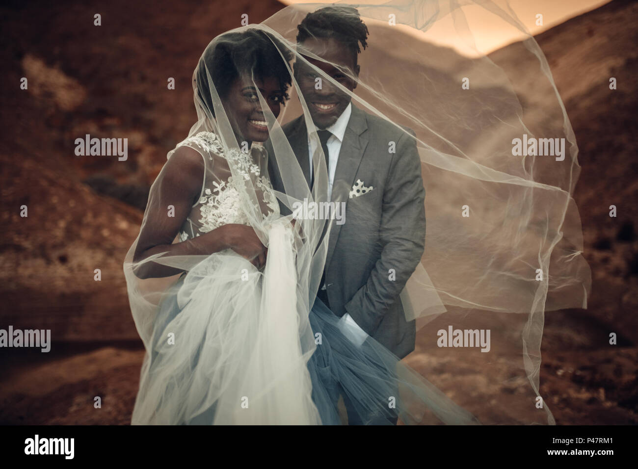 Black happy newlyweds stand under bridal veil and smile in canyon against beautiful landscape at sunset. Closeup. - Stock Image