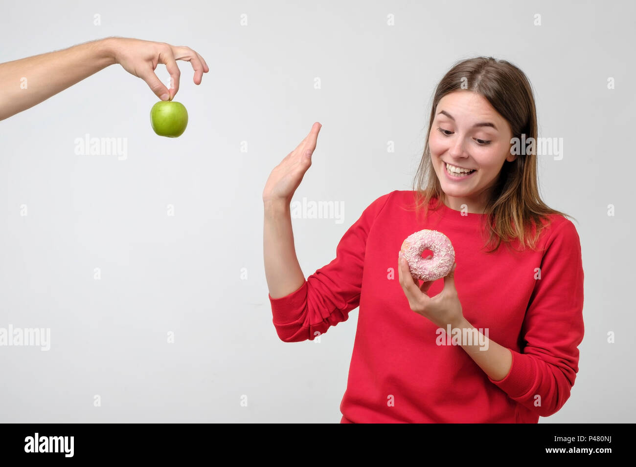 Healthy food and diet concept. Beautiful young woman choosing between fruits and sweets. She prefer a pink donut instead of green apple Stock Photo