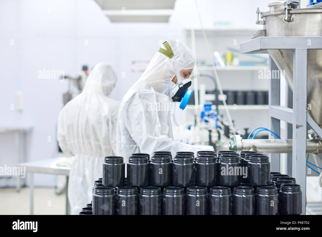 Factory employees working in protective clothing  - Stock Image