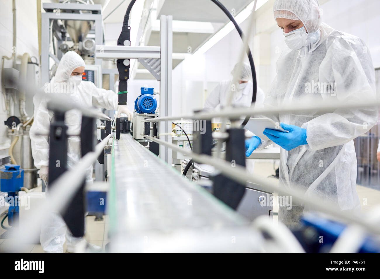 Factory employees working at conveyor belt - Stock Image