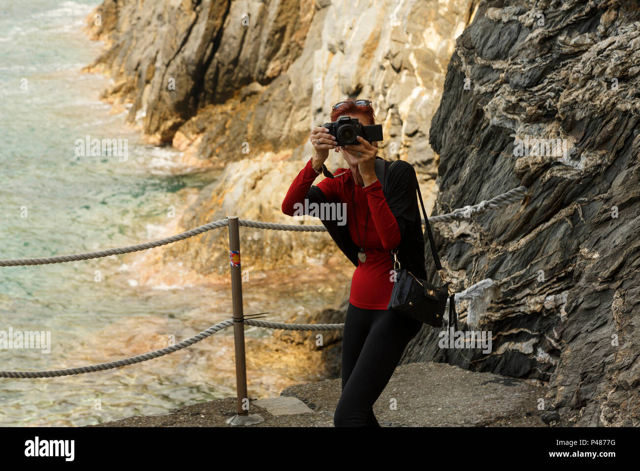 Solo female tourist photographer-videographer candidly shooting against rocky seacoast background, Manarola, Cinque Terre, Italy - Stock Image