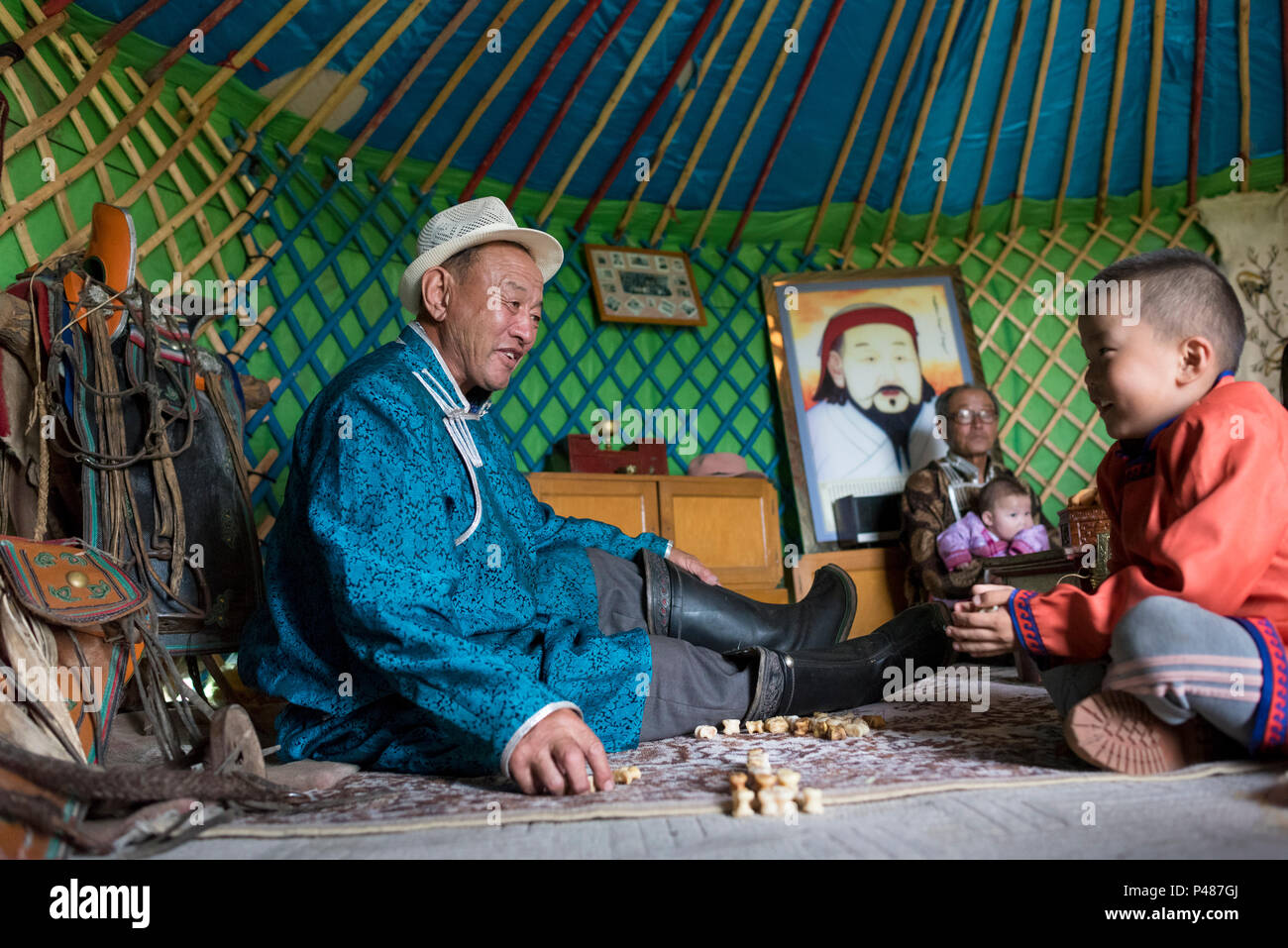 Father and son play game with animal bones inside their summertime yurt, Zhenglanqi Wuyi, Inner Mongolia - Stock Image