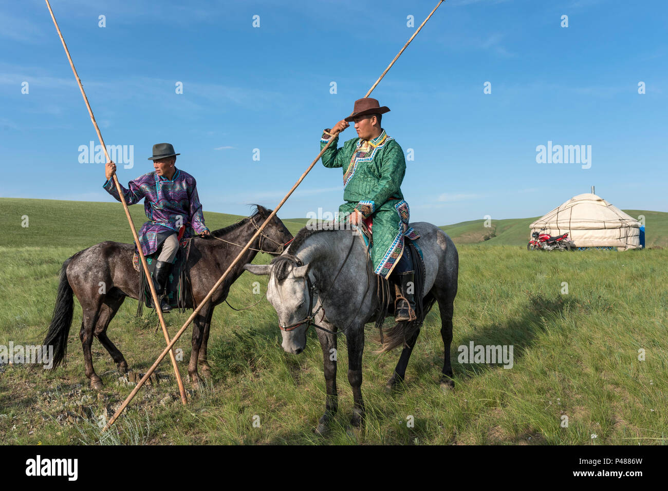 Horseman dressed in traditional costume hold rope and pole urga or lassoe, Inner Mongolia, China - Stock Image