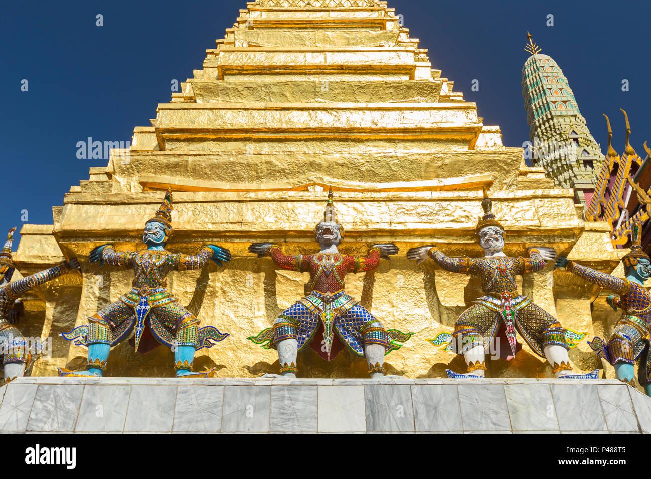 Guardian statues on the base of a golden chedi at Wat Phra Kaeo, the Royal Grand Palace, Bangkok,Thailand - Stock Image
