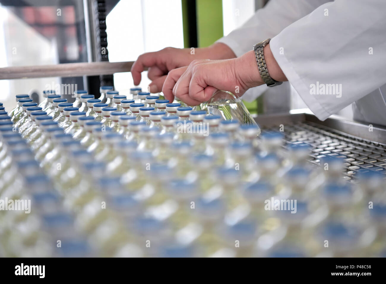 production and filling of drugs in a pharmaceutical conveyor belt with bottles and a worker - Stock Image
