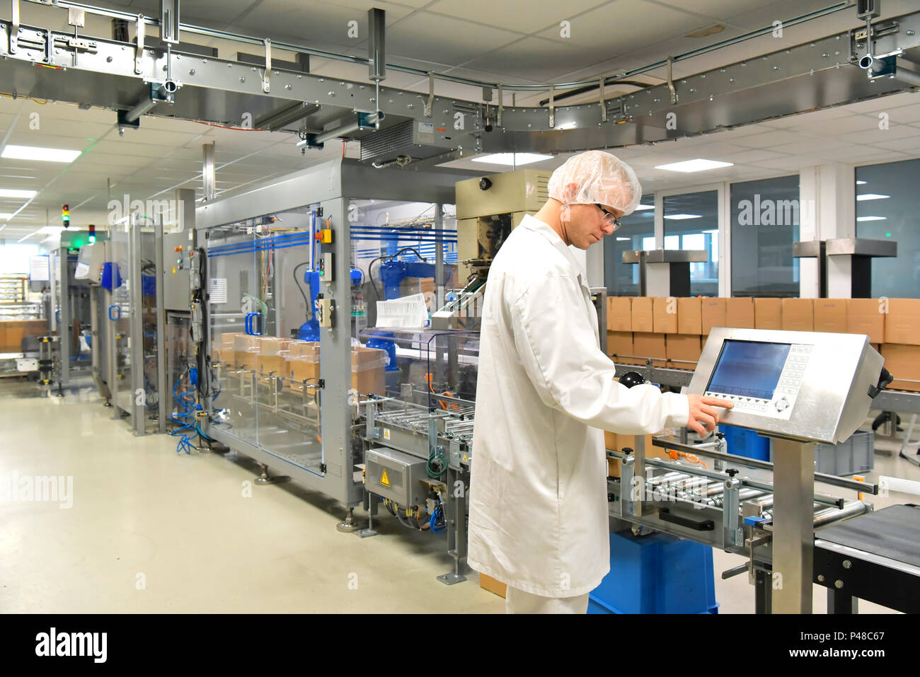 Conveyor belt worker operates a robot that transports insulin bags - modern factory for the production of medicines in the healthcare sector - Stock Image