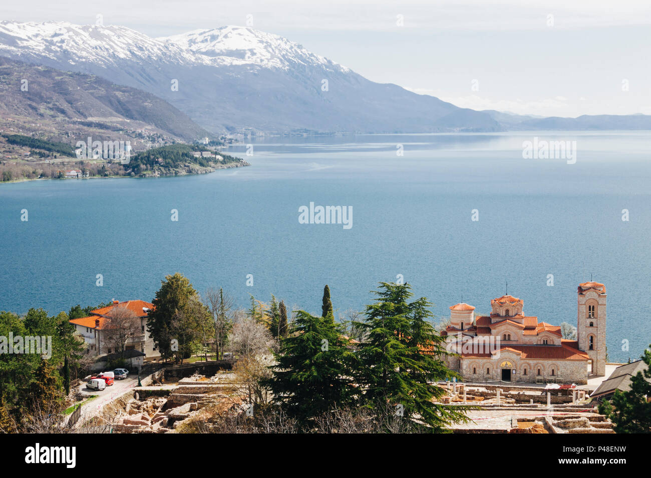 Ohrid, Republic of Macedonia : Ohrid lake landscape with snowcapped mountain and Byzantine Church of the Saints Clement and Panteleimon founded  by St - Stock Image
