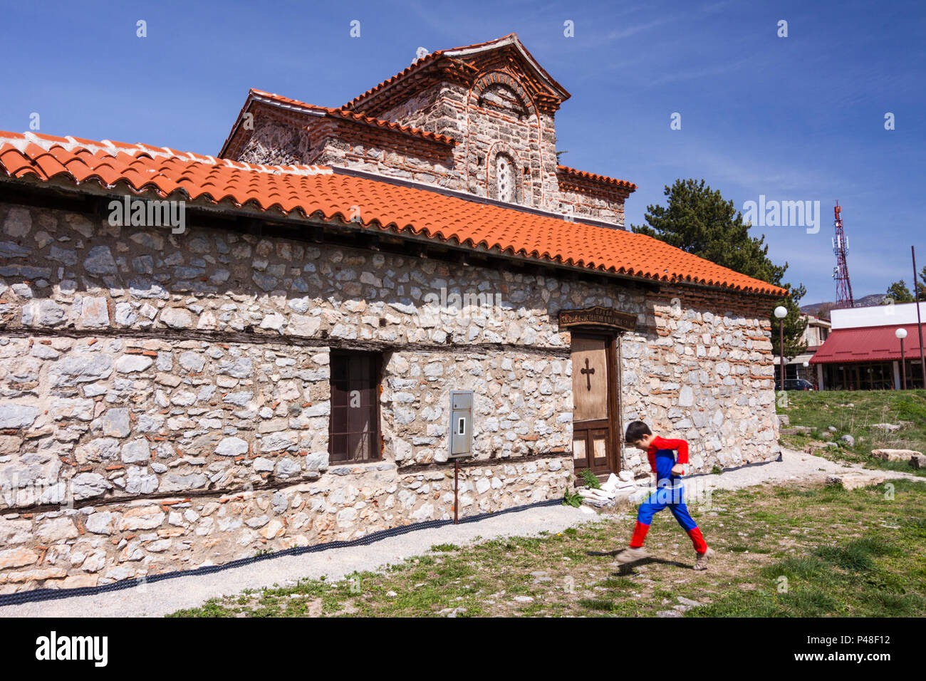 Ohrid, Republic of Macedonia : A child in an Spiderman costume walks past the Holy Mother of God Peribleptos church (1295) one of the oldest churches  - Stock Image