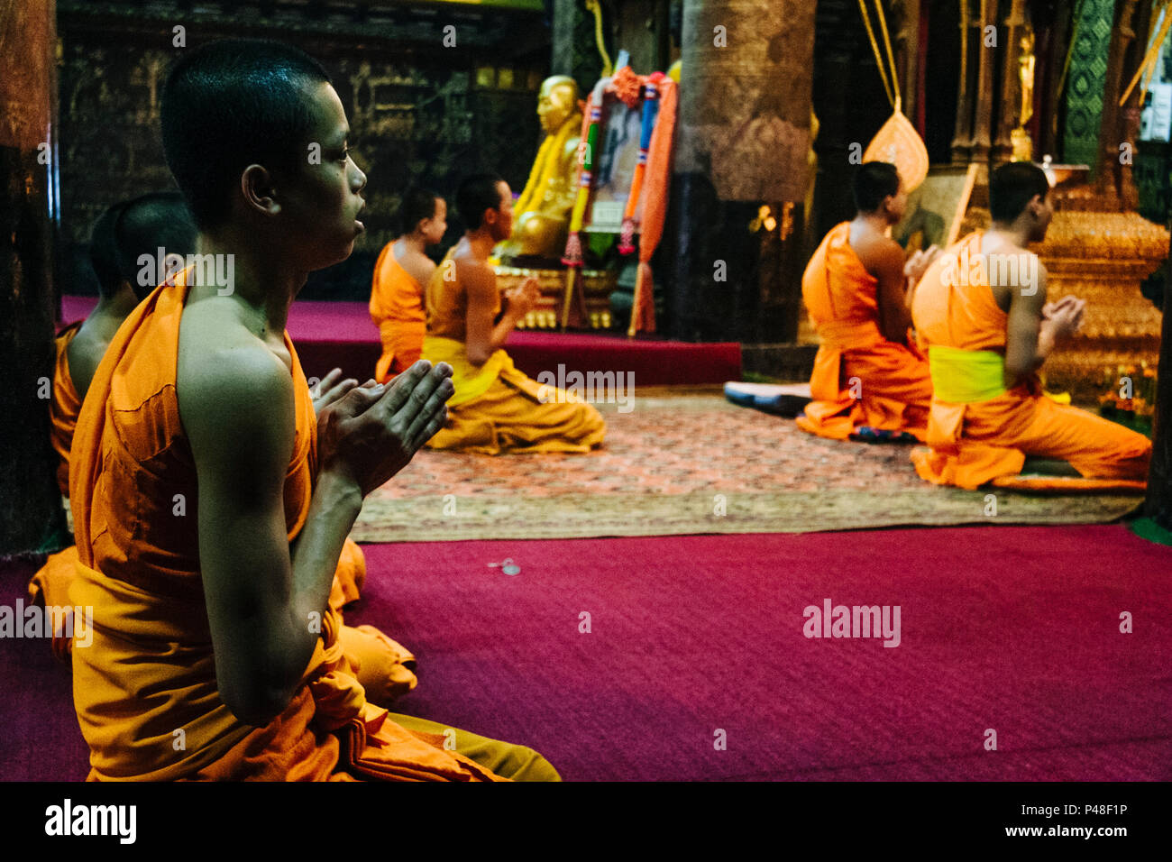 Luang Prabang or Louangphabang, Laos, Southeast Asia : Laotian Buddhist monks pray inside Wat Mai Suwannaphumaham, or Wat Mai, built in 1750 and the l - Stock Image