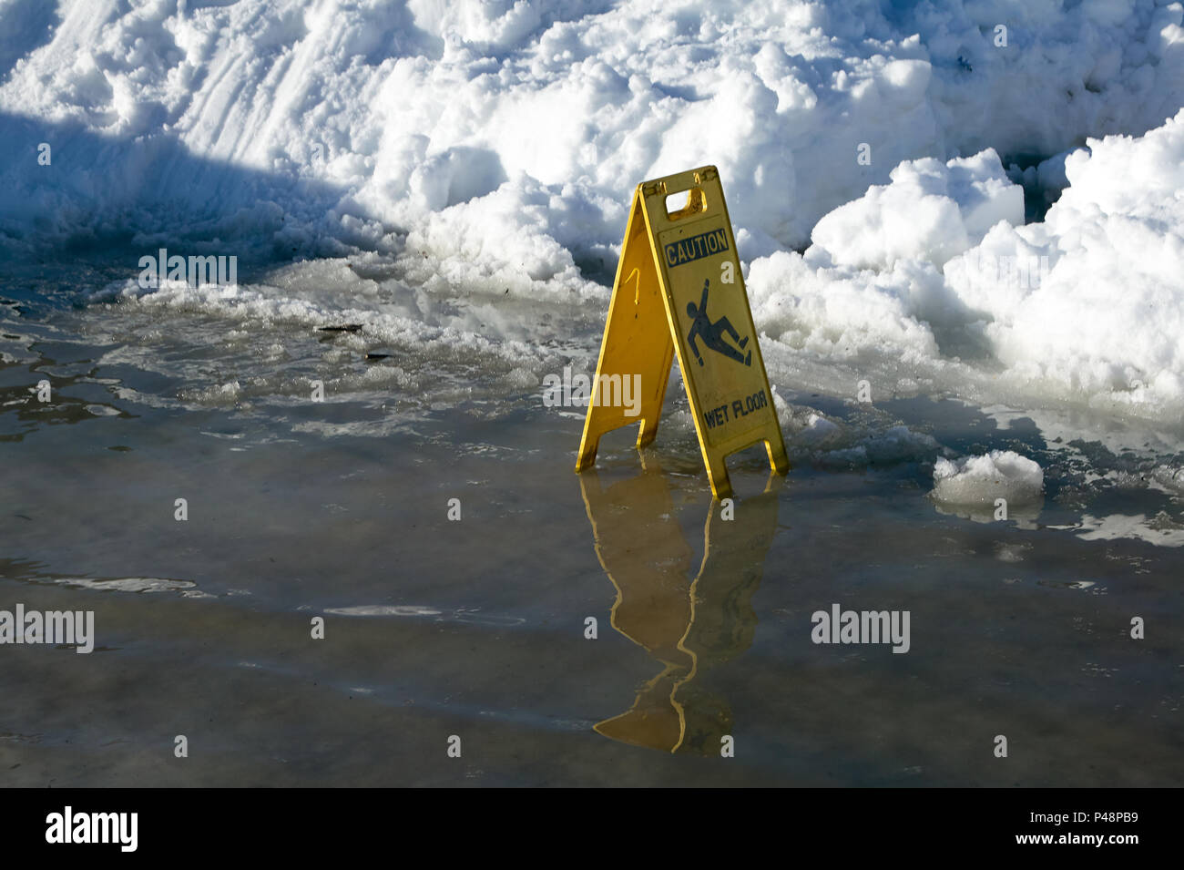 Warning sign for a slippery or icy road surface in front of a melting bank or drift of winter snow - Stock Image