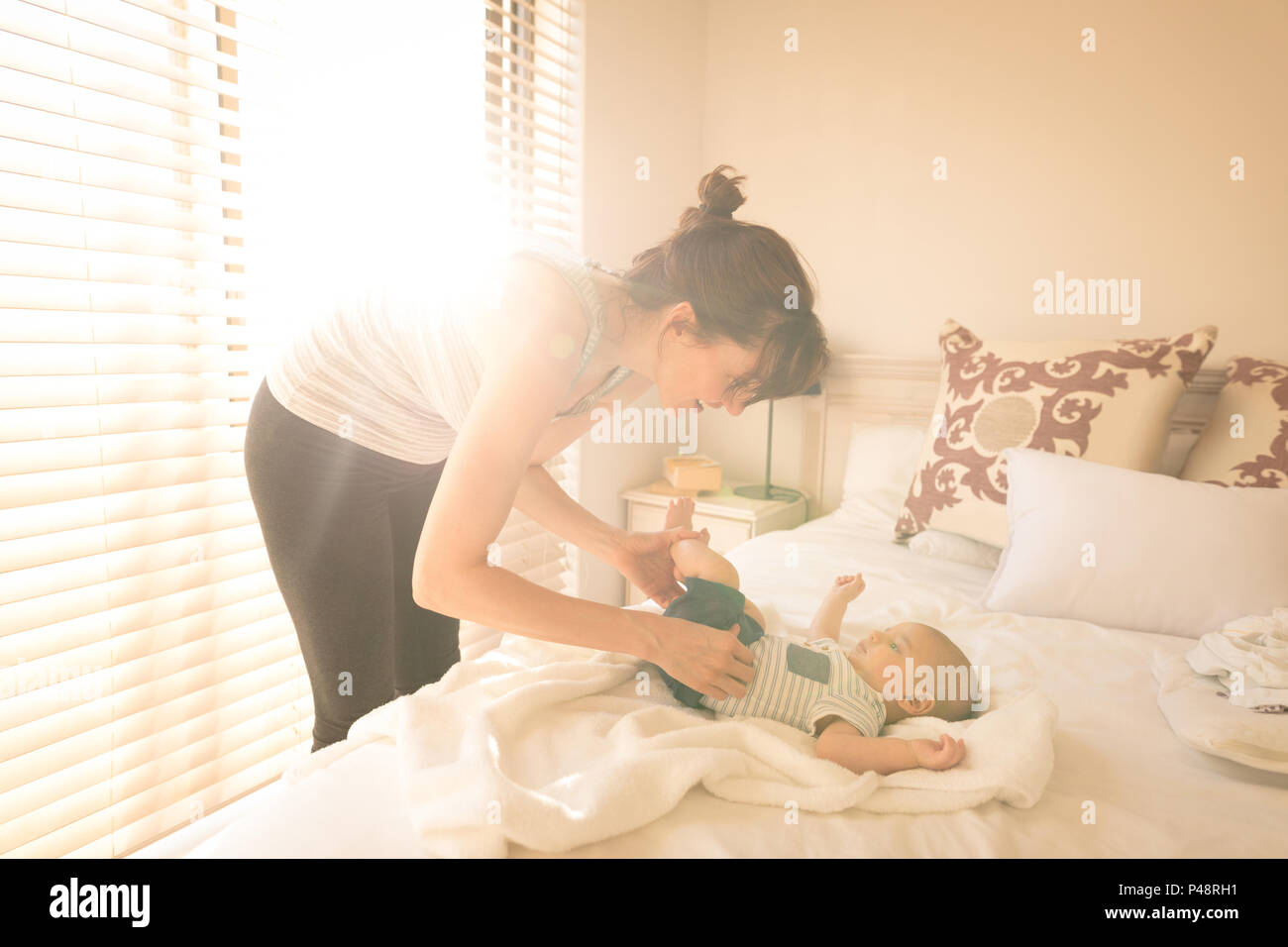 Cute little baby getting dressed by her mother on bed in the bedroom Stock Photo