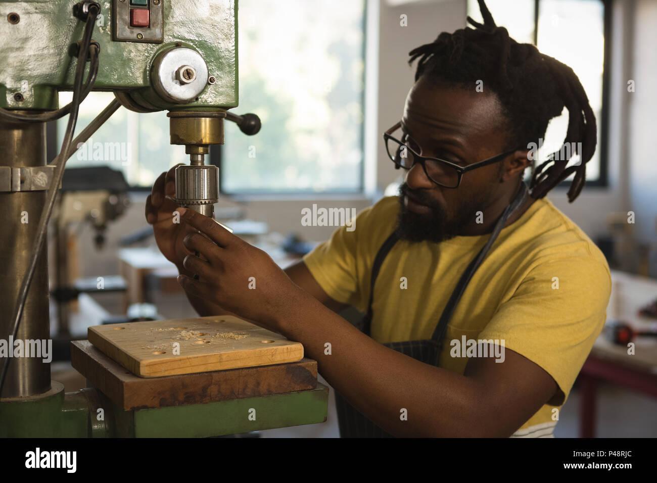 Carpenter adjusting drilling machine - Stock Image