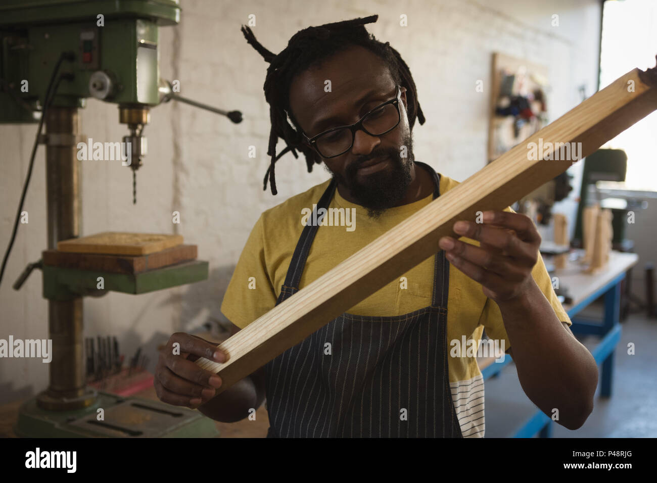 Carpenter looking at wooden plank - Stock Image