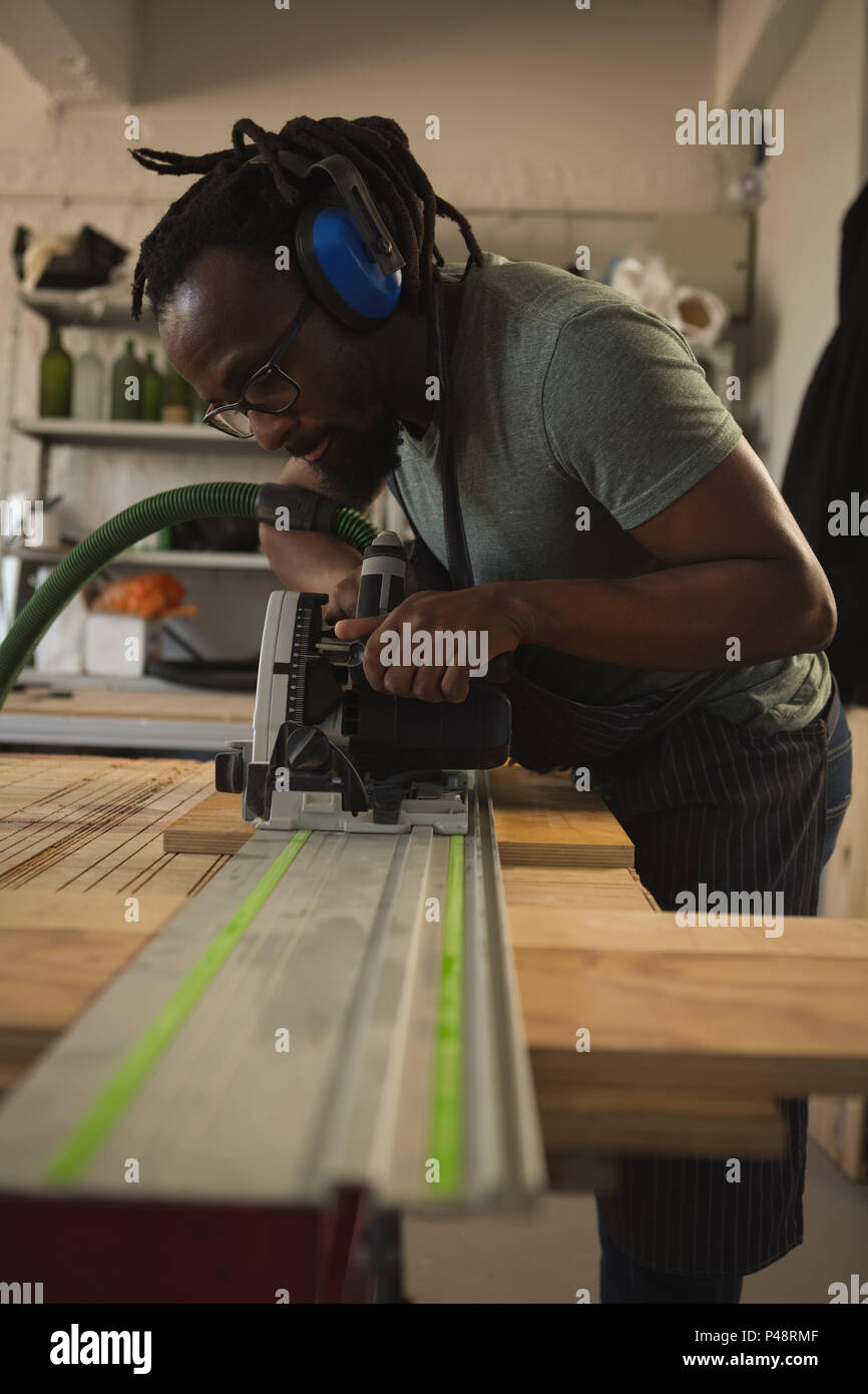 Carpenter leveling wood with polishing machine - Stock Image