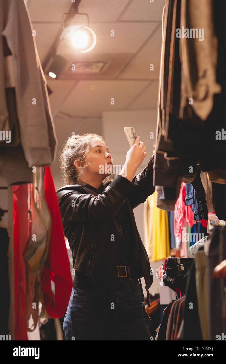 Beautiful woman using mobile phone while shopping - Stock Image