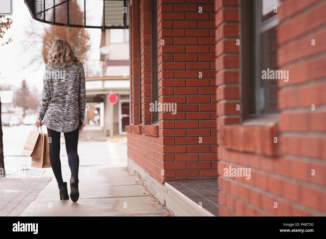Rear view of woman with shopping bag walking in passage - Stock Image