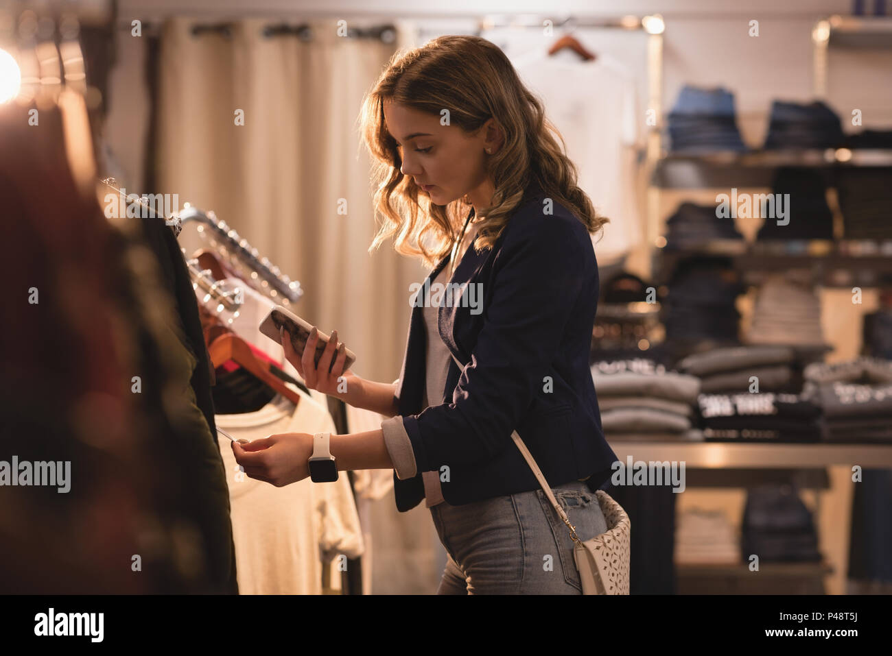 Beautiful woman looking at price tag - Stock Image