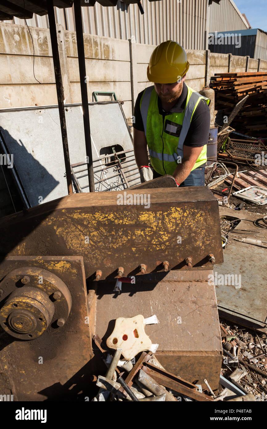Worker working in scrapyard - Stock Image