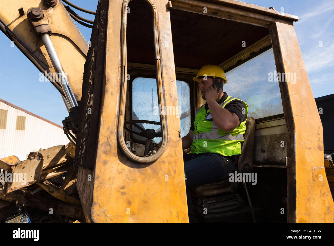 Worker talking on the phone while operating the crane - Stock Image