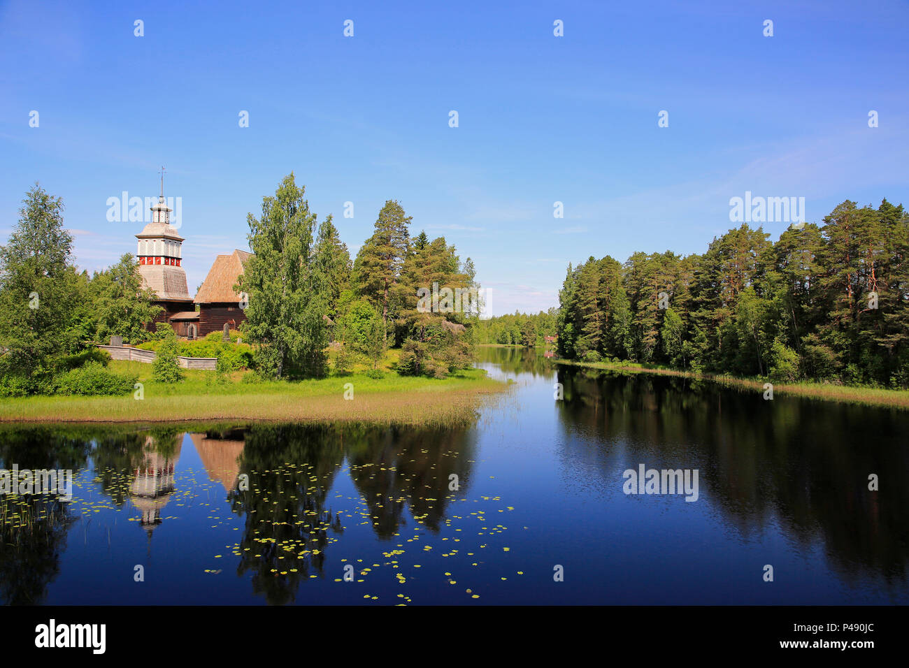 Finnish blue lake and sky landscape with UNESCO World Heritage site, old wooden church of Petajavesi, Finland in summer. The church was built 1763-65. - Stock Image