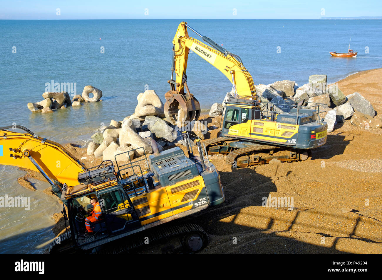 Hastings, UK. Building sea defences and strengthening the Harbour Arm, with granite boulders transported by sea from Falmouth in Cornwall. - Stock Image