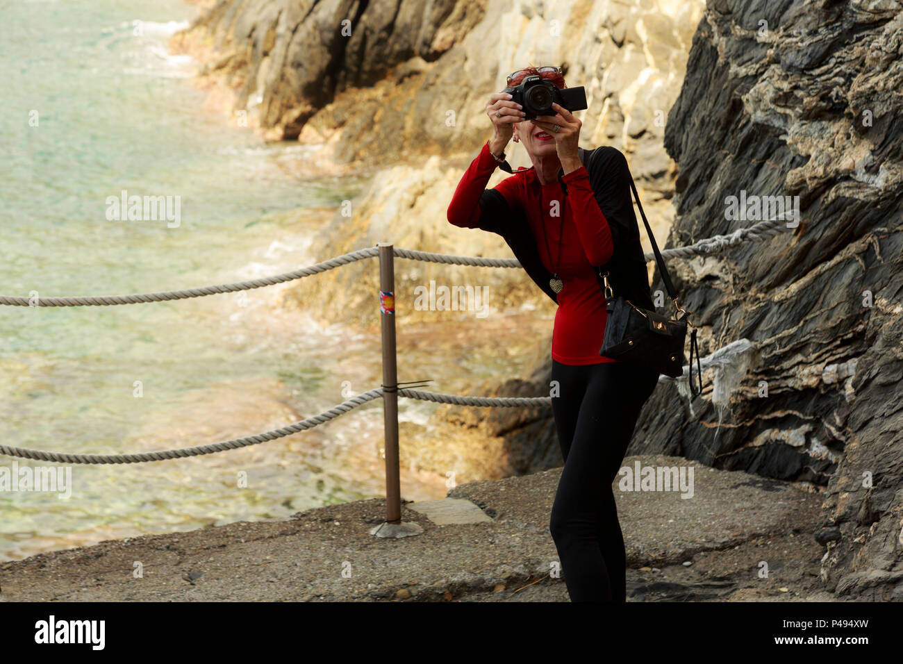 Woman tourist photographer-videographer candidly shooting against rocky seacoast background in Cinque Terre, Italy - Stock Image