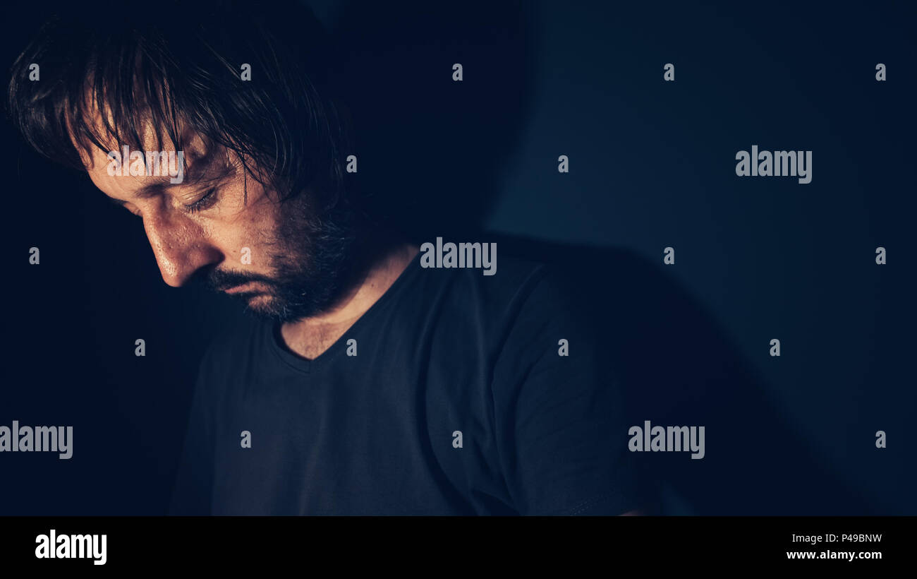 Mental health and depression concept, sad depressed man sulking in dark interior - Stock Image