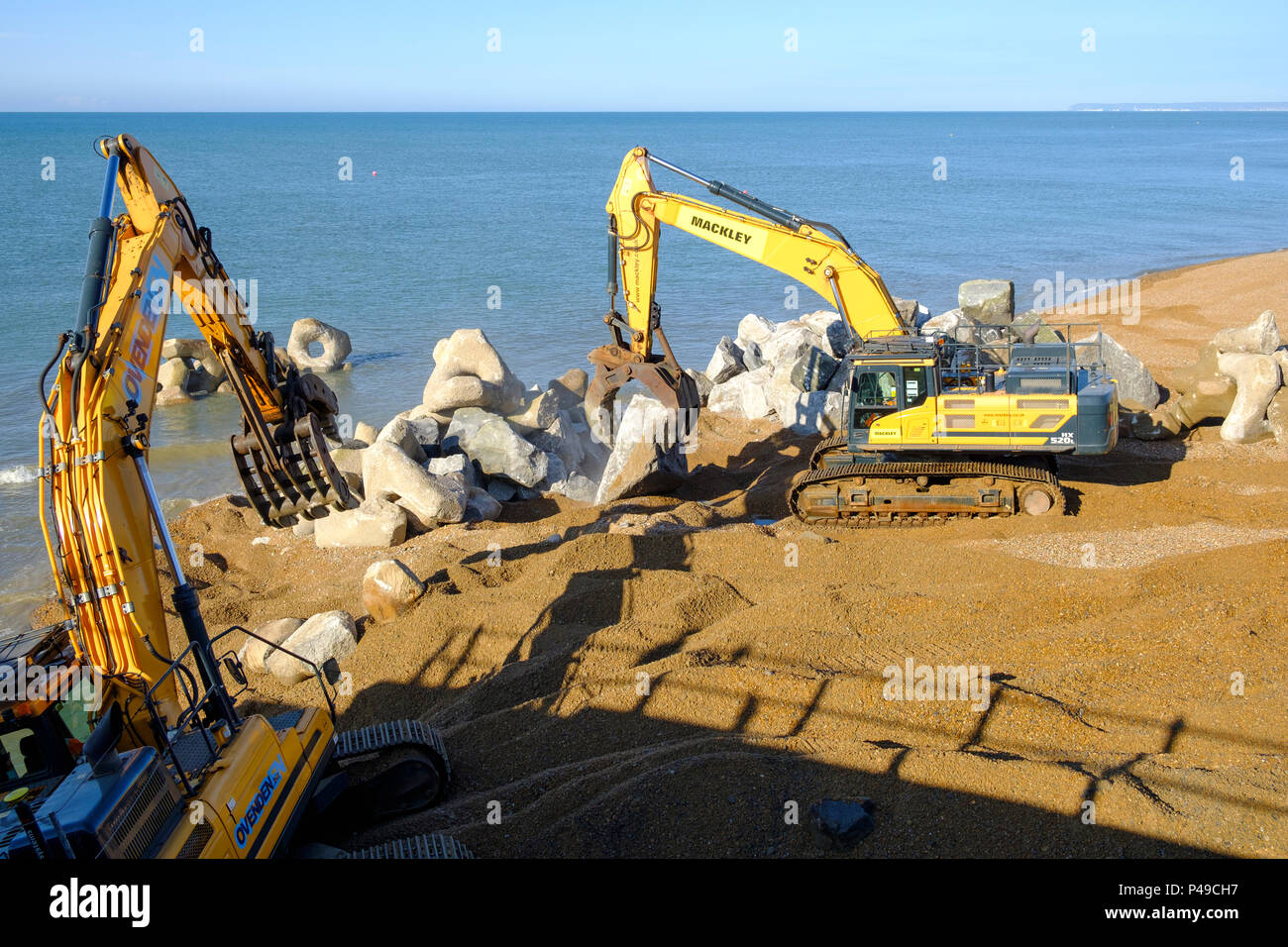 Hastings UK. Building sea defences and strengthening the Harbour Arm, with granite boulders transported by sea from Falmouth in Cornwall - Stock Image