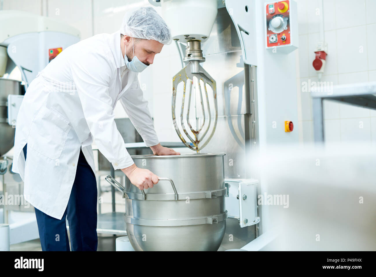 Confectionery factory employee working with machinery - Stock Image