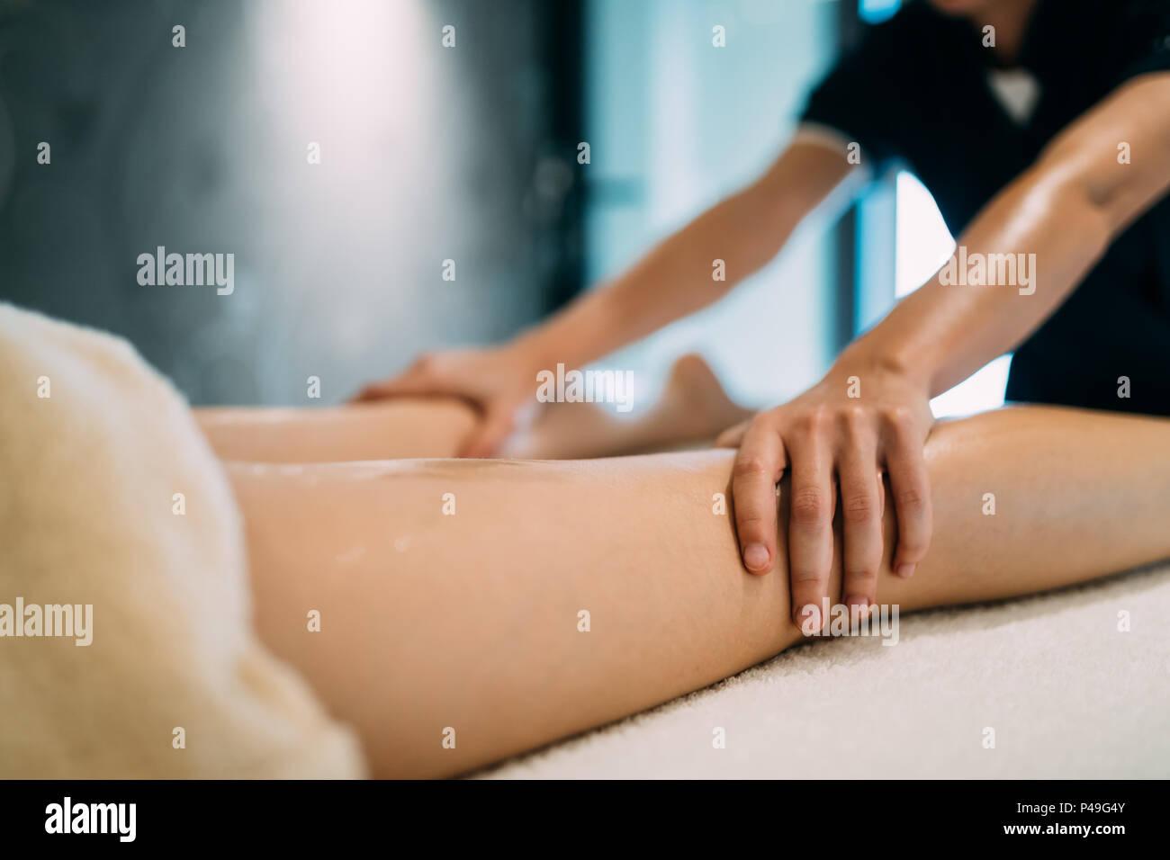 Masseur massaging masseuse during therapeutic tretment - Stock Image