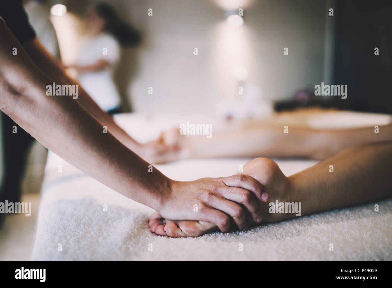 Foot and sole massage in therapeutic relax treatment - Stock Image