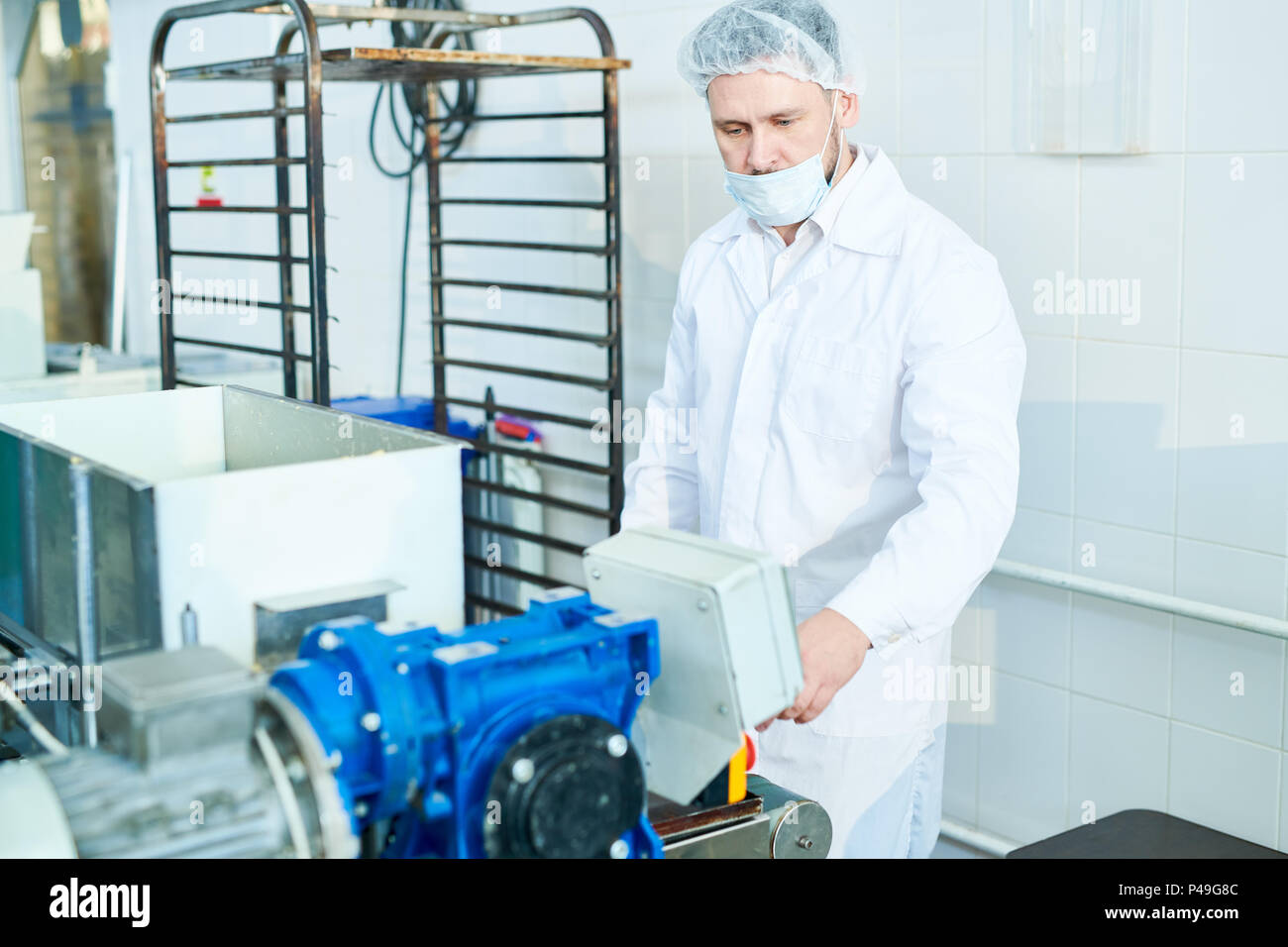 Confectioner working with machine at factory - Stock Image