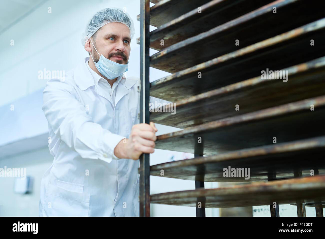 Man in white uniform moving shelves for bread - Stock Image