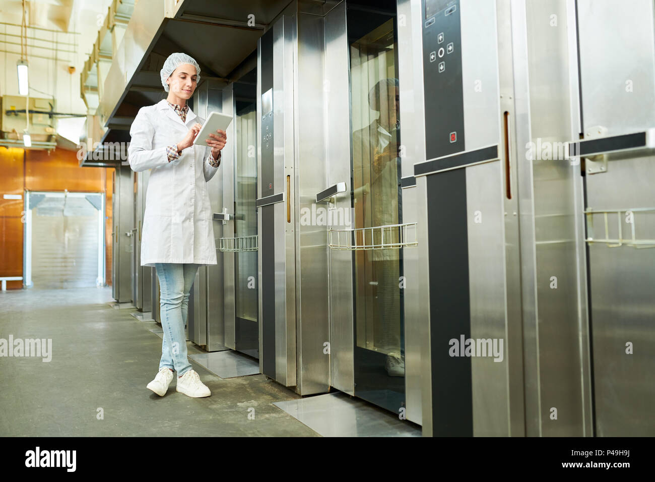 Woman standing in lab coat and using tablet - Stock Image